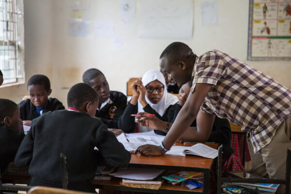 Students work with their mentor at Marangu Hills Secondary School in Tanzania.