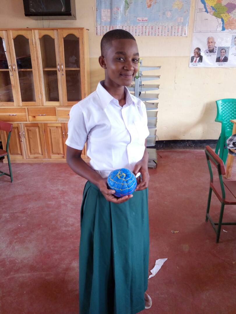 A young student smiles and presents her an object she designed to the camera. The object is a blue sphere with horizontal and vertical lines sewn into it.